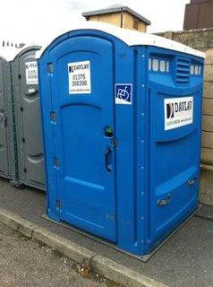 Mobile Toilette für Rollstuhlnutzerinnen und Rollstuhlnutzer - Das Fot zeigt eine blaue mobile Toilette, welche ausreichend Raum für Nutzerinnen und Nutzer mit Rollstuhl bietet. Die Toilette wurde jedoch am Straßenrand auf dem Gehweg aufgestellt. Der Bordstein wurde dabei nicht berücksichtigt. So ist diese Toilette nicht stufenfrei zu befahren.