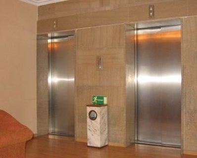 Zwei nebeneinander liegende Eingangstüren zu einer Liftanlage in einem Gebäude. Das Tableau mit den Rufknöpfen ist zu hoch angebrachte und der Zugang zu einer der Türen wird durch einen Abfallbehälter erschwert.