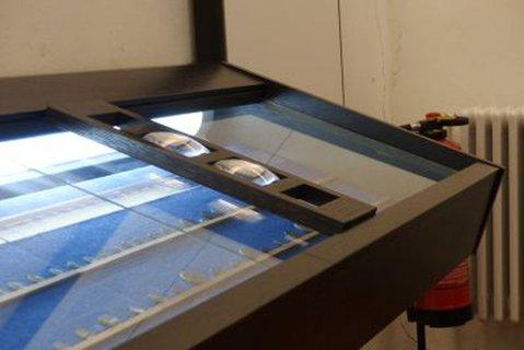 Vergrößerungsglas in einem Museum in Regensburg. Der Träger der Lupe kann seitlich bewegt werden. Die Lupe selbst ist auch in diesem Träger von oben nach unten zu bewegen.