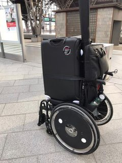 Rollstuhl mit Koffer drauf