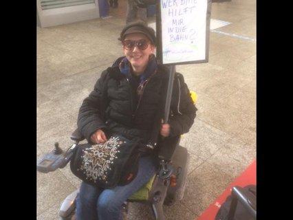 """Meli Fischer mit ihrem E-Rolli und Plakat """"Wer hilft mir in die Bahn"""", das sich auf neue Barrieren der U-Bahn bezieht"""