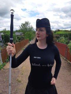Jennifer Sonntag mit Blindenstock, Hut, und T-Shirt mit der Aufschrift