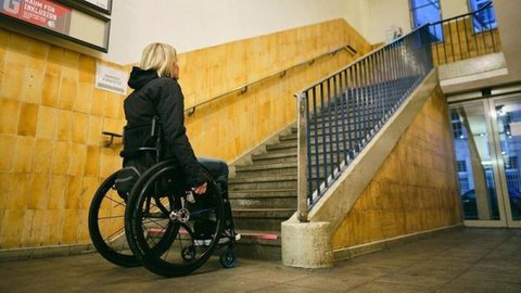 Bild zur Petition auf change.org: Frau, die einen Rollstuhl nutzt, steht vor einer Treppe