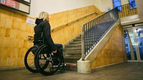 Frau, die einen Rollstuhl nutzt, steht vor einer Treppe