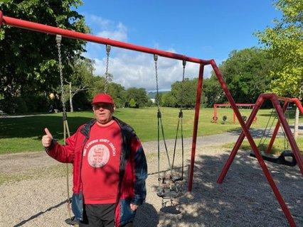 Ottmar Miles-Paul im Kassler Goethepark vor der Schaukel mit Blick über den Park und dem Herkules in der Ferne