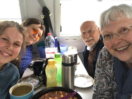Bild von Ellen Keune, ihrer Assistentin und ihren Eltern beim Kaffeetrinken im Campingbus