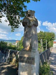 Großer Bär aus Stein am Anfang der Berliner Brücke in Kassel mit blauem Himmel im Hintergrund und dem Kasseler Herkules in Sichtweite