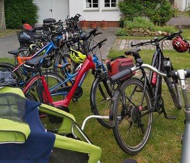12 Fahrräder stehen in der Reihe aufgestellt vor einem Haus