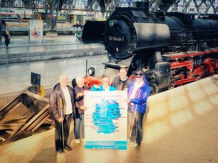 Reisegruppe Niemand mit Tourkarte am Leipziger Hauptbahnhof vor historischer Lok