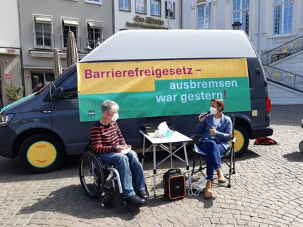 Dr. Sigrid Arnade im Gespräch mit Christina Marx von der Aktion Mensch am Mehr Barrierefreiheit Wagen auf dem Marktplatz in Bonn