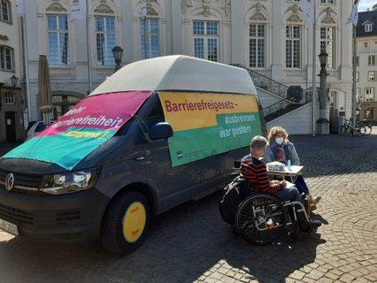 Dr. Sigrid Arnade im Gespräch mit Dagmar Greskamp am Mehr Barrierefreiheit Wagen auf dem Bonner Marktplatz