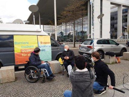 Dr. Sigrid Arnade im Gespräch mit Peter Weiß mit Kamera am Mehr Barrierefreiheit Wagen