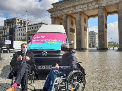Dr. Sigrid Arnade im Gespräch mit Jens Beeck am Mehr Barrierefreiheit Wagen vor dem Reichstag
