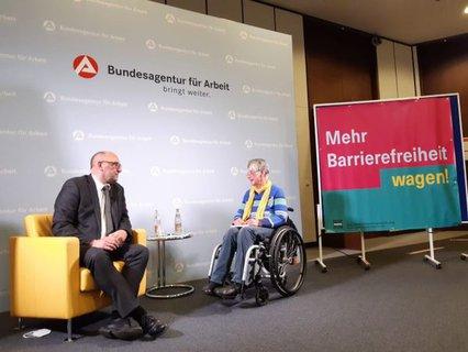 Dr. Sigrid Arnade im Gespräch mit Detlef Scheele mit Transparent des Mehr Barrierefreiheit wagen an der Stellwand