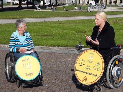 Dr. Sigrid Arnade im Gespräch mit Stephanie Aeffner mit Schildern: Noch 49 Tage für ein gutes Barrierefreiheitsrecht an den Rollstühlen
