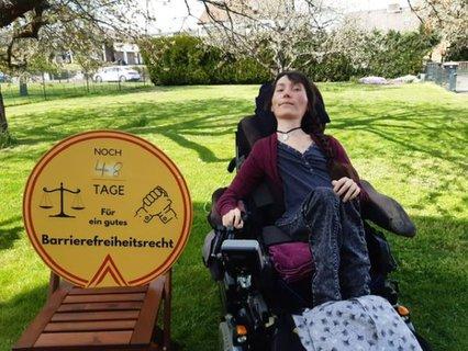 Marleen Soetandi mit Elektrorollstuhl und großem Logo: Noch 48 Tage für ein gutes Barrierefreiheitsrecht